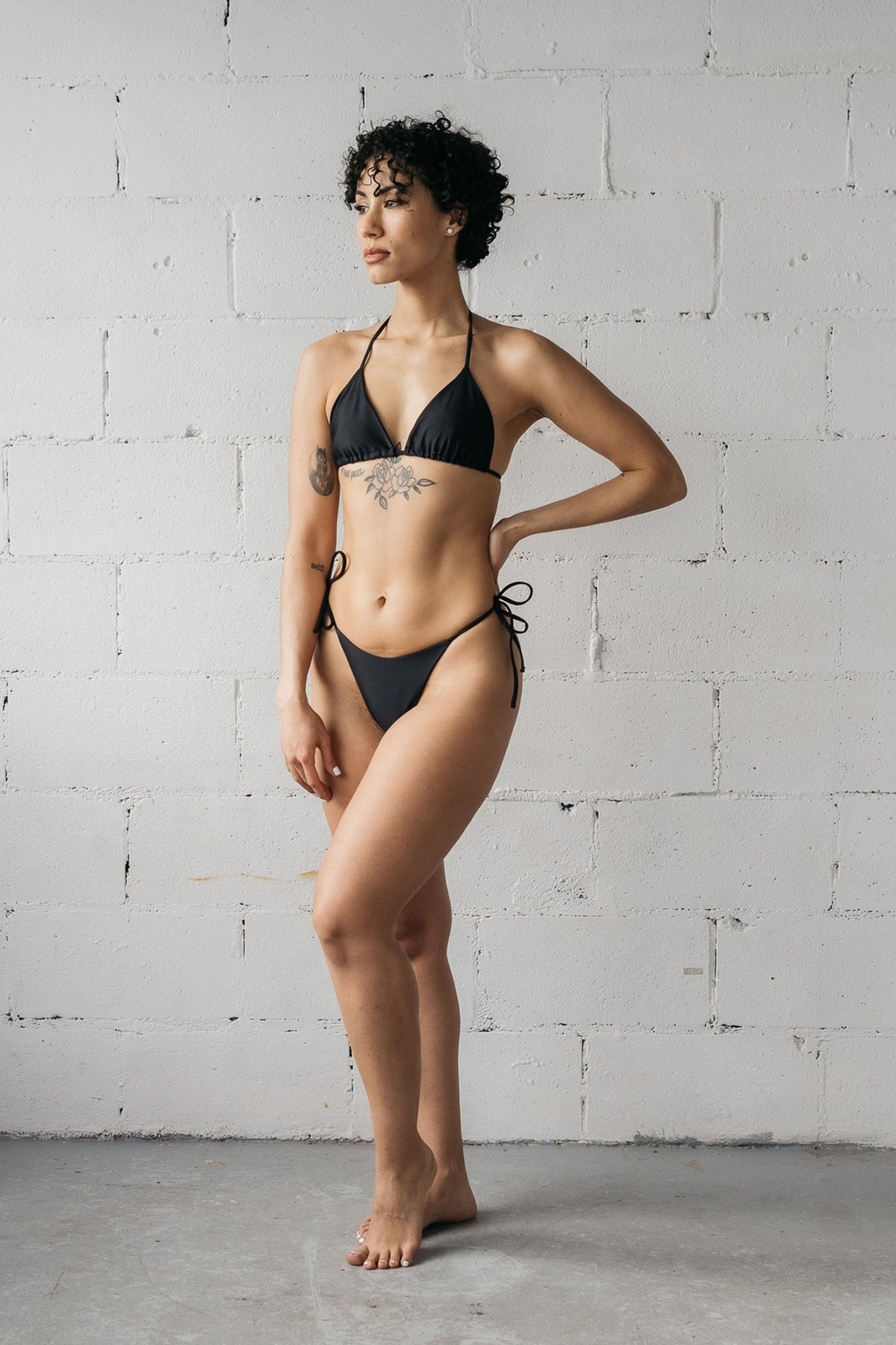A woman standing with one hand on her hip and the other relaxed by her side wearing adjustable black triangle string bikini bottoms with a matching black triangle string bikini top.