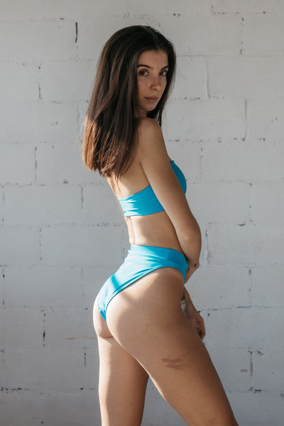 A woman standing looking over her shoulder in front of a white brick wall wearing bright turquoise high cut bikini bottoms with a matching bright turquoise strapless bandeau bikini top.