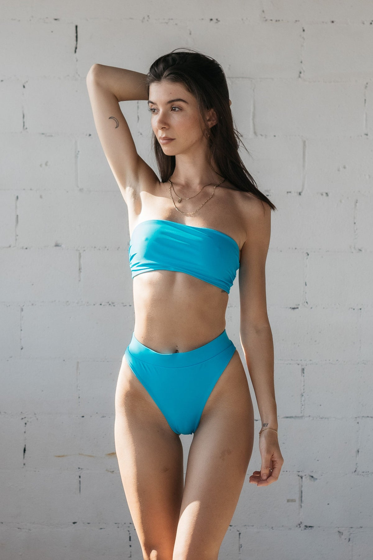 A woman standing in front of a white brick wall wearing bright turquoise high cut bikini bottoms with a matching bright turquoise strapless bandeau bikini top.