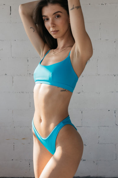 A woman standing with her arms above her head wearing bright turquoise v cut bikini bottoms and a matching bright turquoise scoop neck bikini top.