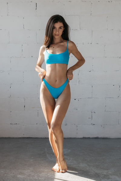 A woman standing with one leg bent in front of the other and her hands on her hips wearing bright turquoise high cut bikini bottoms and a matching bright turquoise bikini top with a scoop neckline.