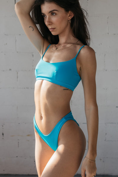 A woman standing in front of a white wall looking into the distance wearing bright turquoise high cut bikini bottoms and a matching bright turquoise bikini top with a scoop neckline.