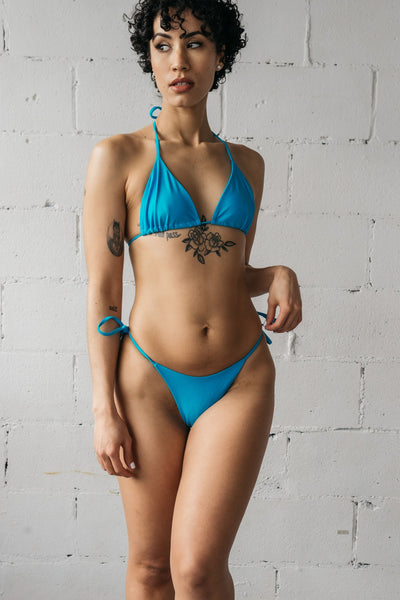 A woman standing with one hand hovered above her hip wearing turquoise triangle string bikini bottoms with a matching turquoise string triangle bikini top.