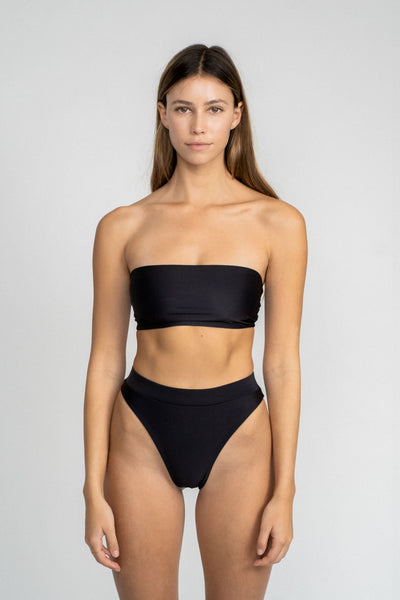 A woman standing with her arms by her side in front of a white wall wearing black high waisted bikini bottoms with a matching black strapless bandeau bikini top.