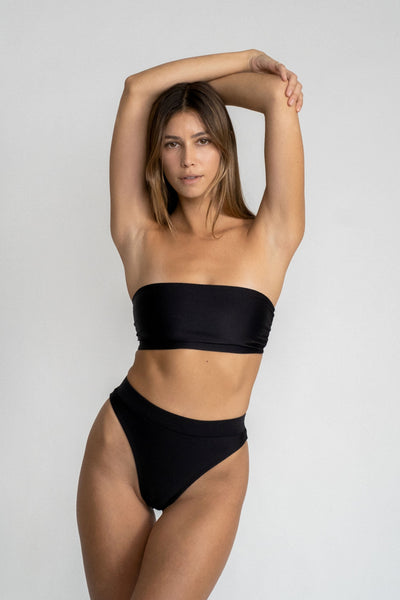 A woman standing with her arms above her head wearing black high waisted bikini bottoms with a matching black strapless bandeau bikini top.