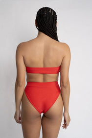 The back of a woman with her arms by her side wearing bright red high waisted bikini bottoms with a matching bright red strapless bandeau bikini top.