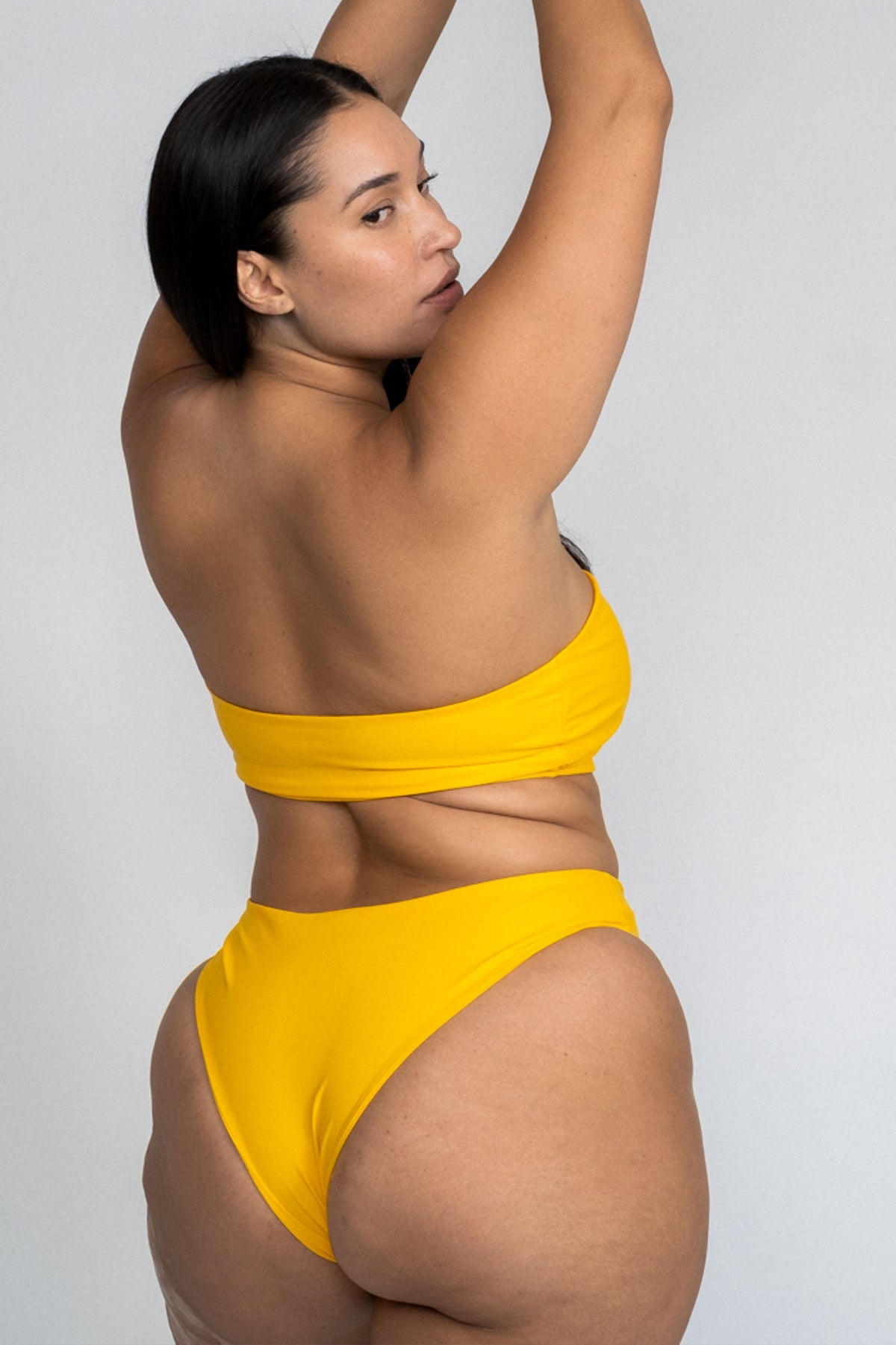 The back of a woman standing looking over her shoulder wearing yellow high cut bikini bottoms with a matching yellow strapless bandeau bikini top.
