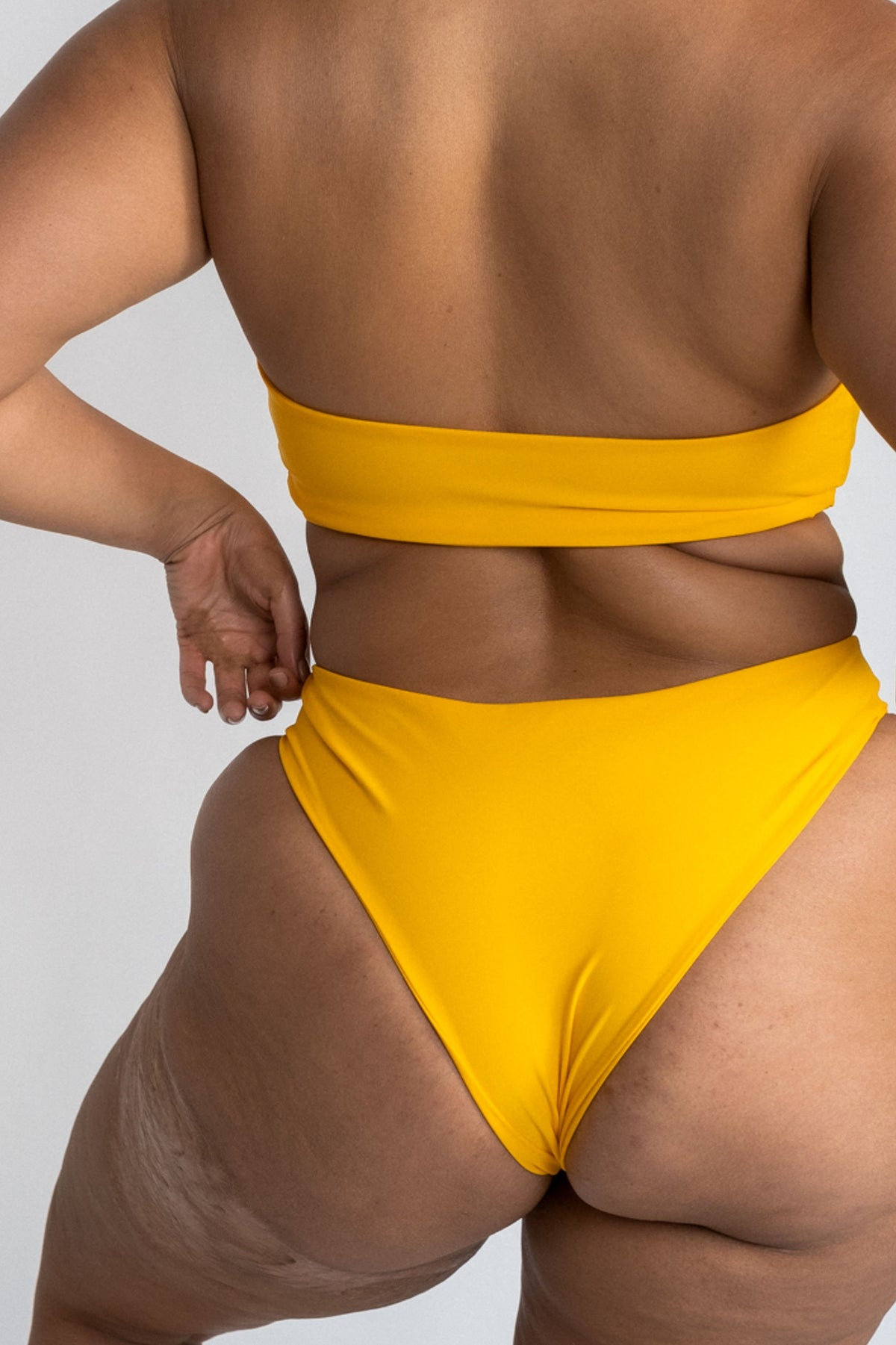 A close up of the back of a woman standing with her hands on her hips wearing yellow high cut bikini bottoms with a matching yellow strapless bandeau bikini top.