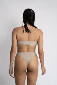 The back of a woman wearing nude high cut bikini bottoms with a matching nude strapless bandeau bikini top.