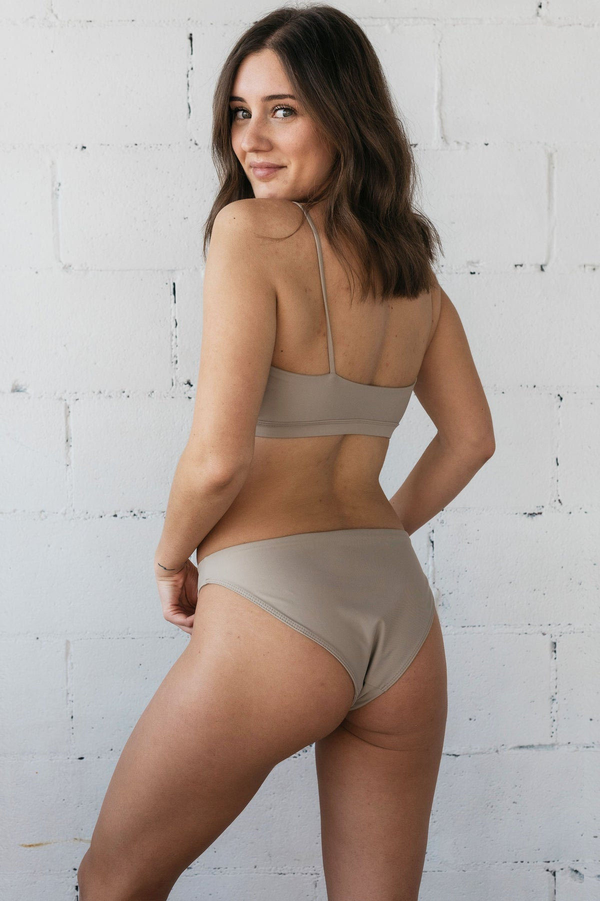 The back of a woman looking over her shoulder wearing beige high cut bikini bottoms and a matching beige bikini top with spaghetti straps.