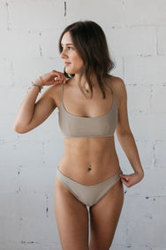 A woman standing looking to the side with one hand on her hip wearing beige high cut bikini bottoms and a matching beige bikini top with a scoop neckline.