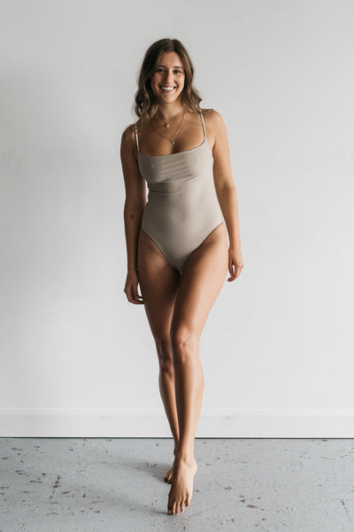 A woman standing with one leg in front of the other wearing a nude one piece swimsuit with white spaghetti straps.
