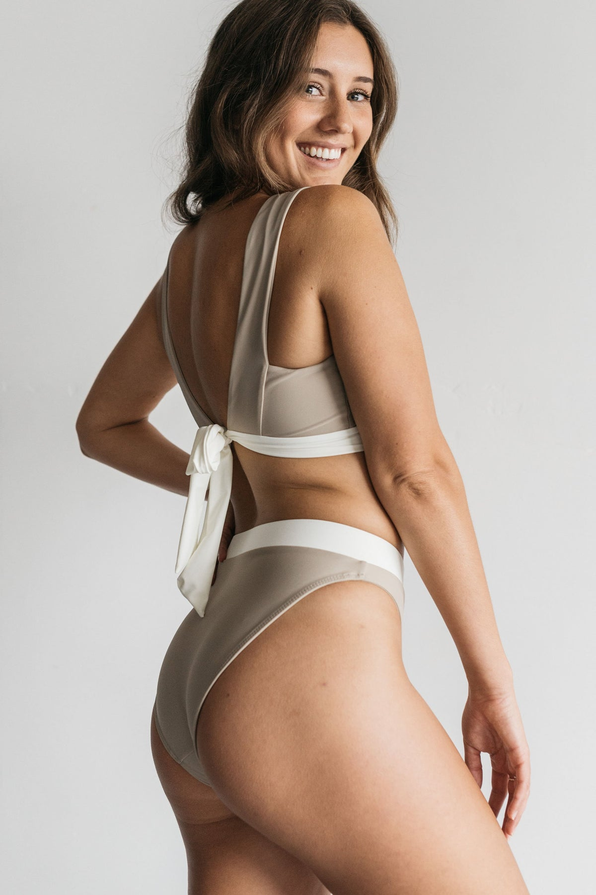 A woman standing in front of a white wall smiling over her shoulder wearing nude high waisted bikini bottoms with a white waistband and a matching nude bikini top with a white adjustable tie.
