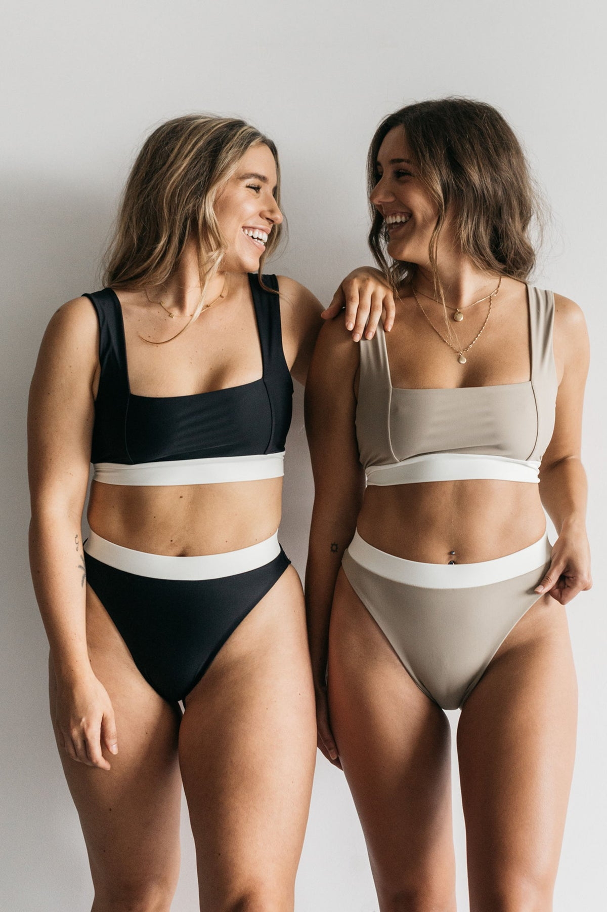 Two women standing in front of a white wall smiling at each other wearing matching bikinis. The woman on the left is wearing black high waisted bikini bottoms with a white waistband and a matching black and white bikini top. The woman on the right is wearing high waisted nude bikini bottoms with a white waistband and a matching nude bikini top with a white band.