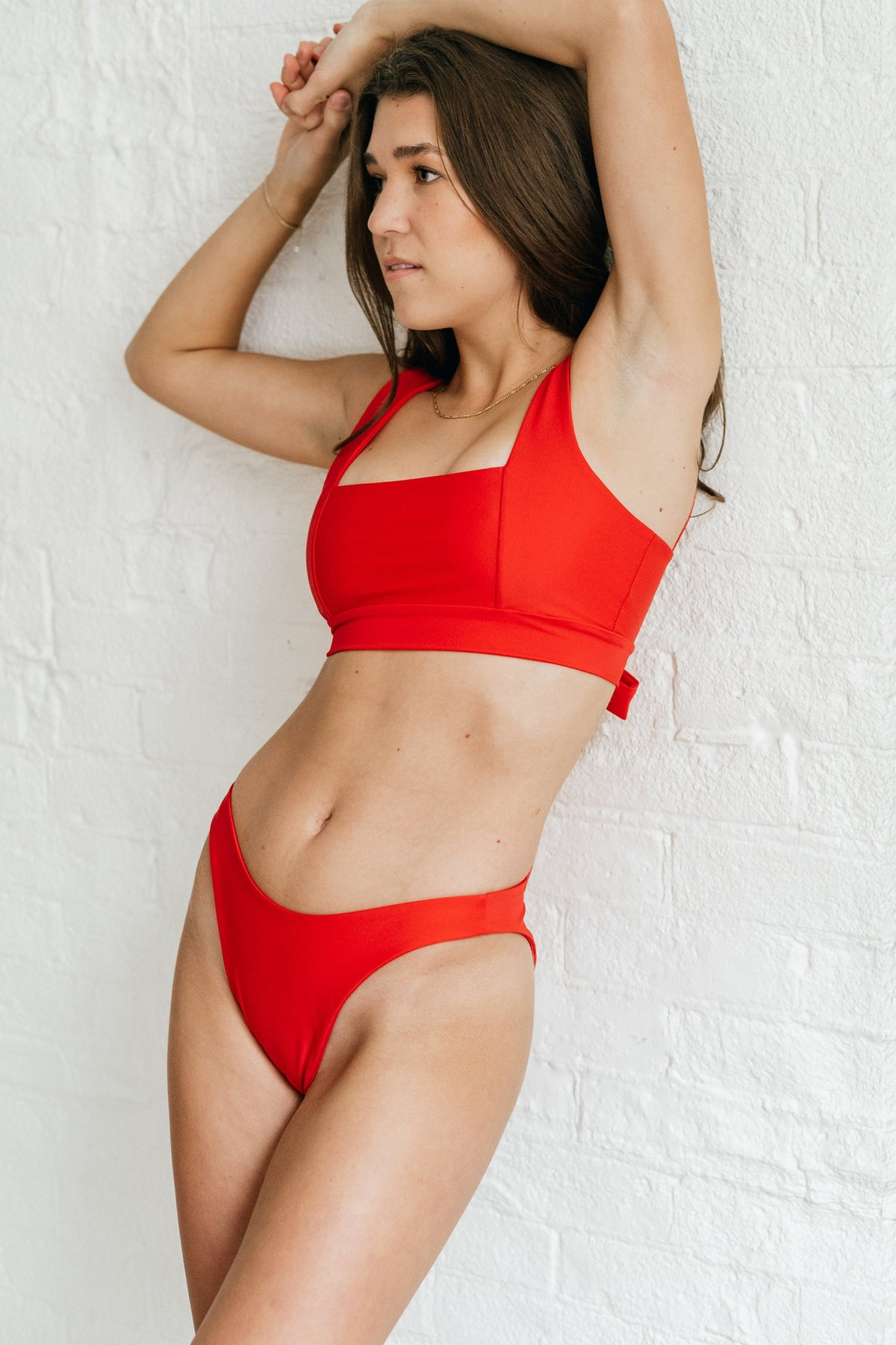 A woman leaning against a white wall with her arms above her head wearing bright red high cut bikini bottoms and a matching bright red bikini top with a square neckline.