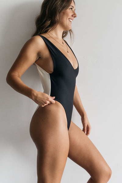 A woman standing to the side wearing a black and white color blocked one piece swimsuit with minimal coverage.