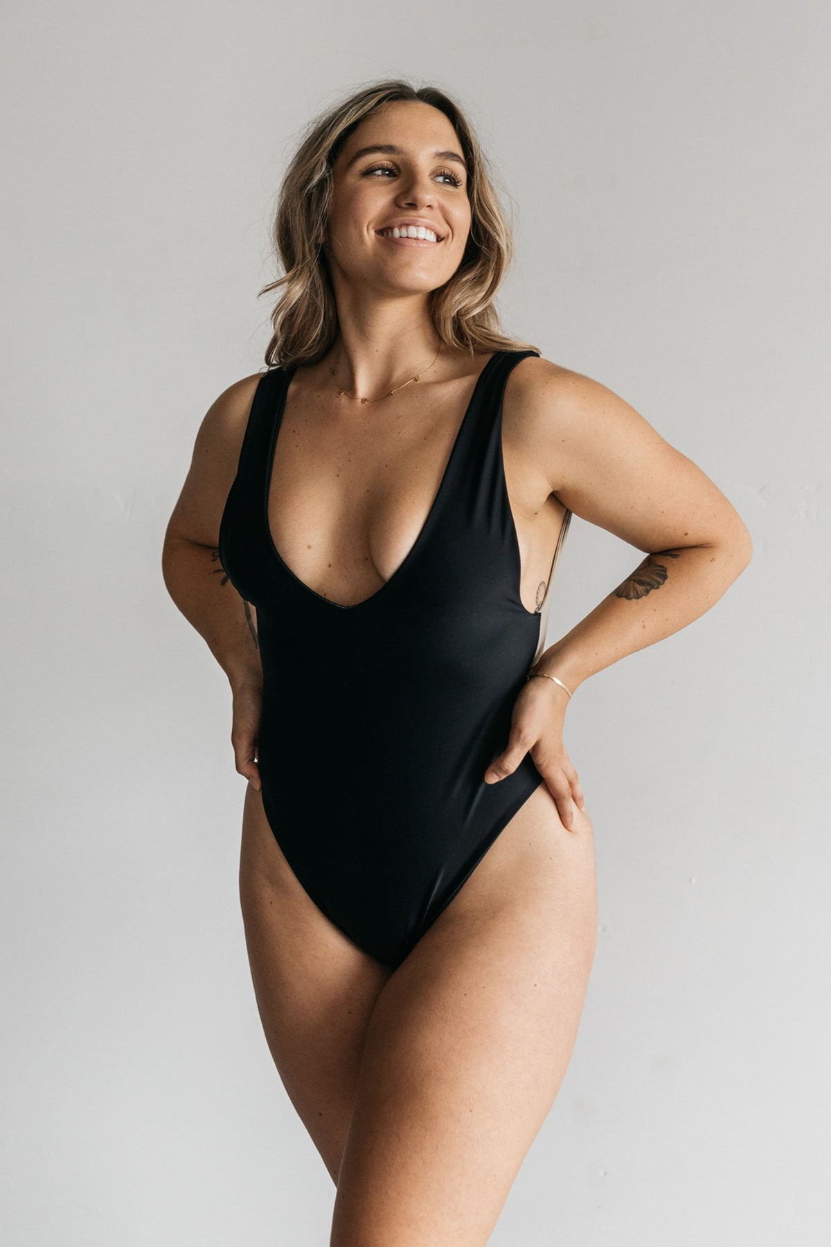 A woman standing with her hands on her hips wearing a wearing a black one piece swimsuit with a v neckline and minimal coverage.