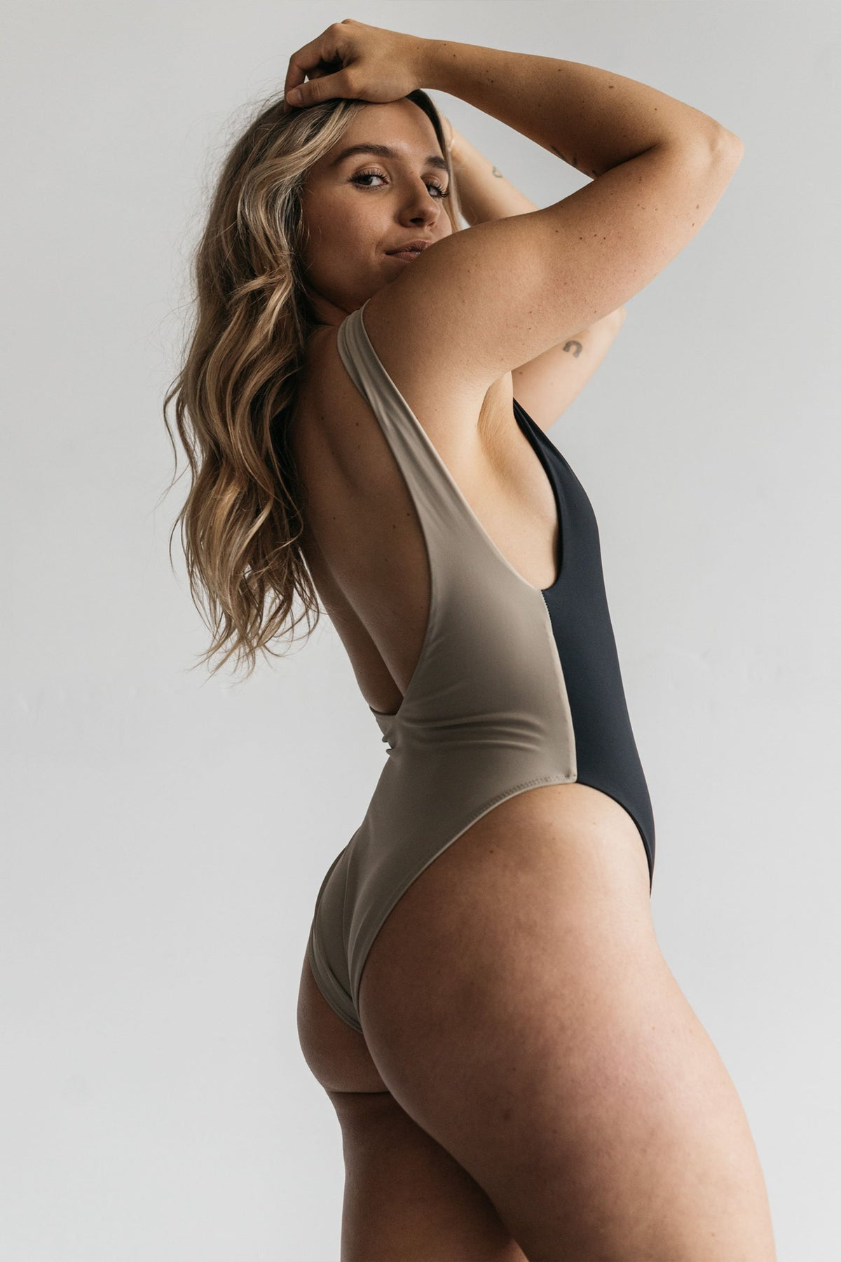 The back of a woman standing with her hands in her hair wearing a black and nude color blocked one piece swimsuit.