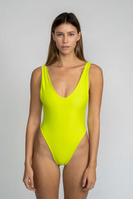 A woman standing wearing a bright neon green one piece swimsuit with a v neckline and minimal coverage.
