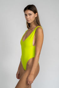 A woman standing to the side wearing a bright neon green one piece swimsuit with a v neckline and minimal coverage.