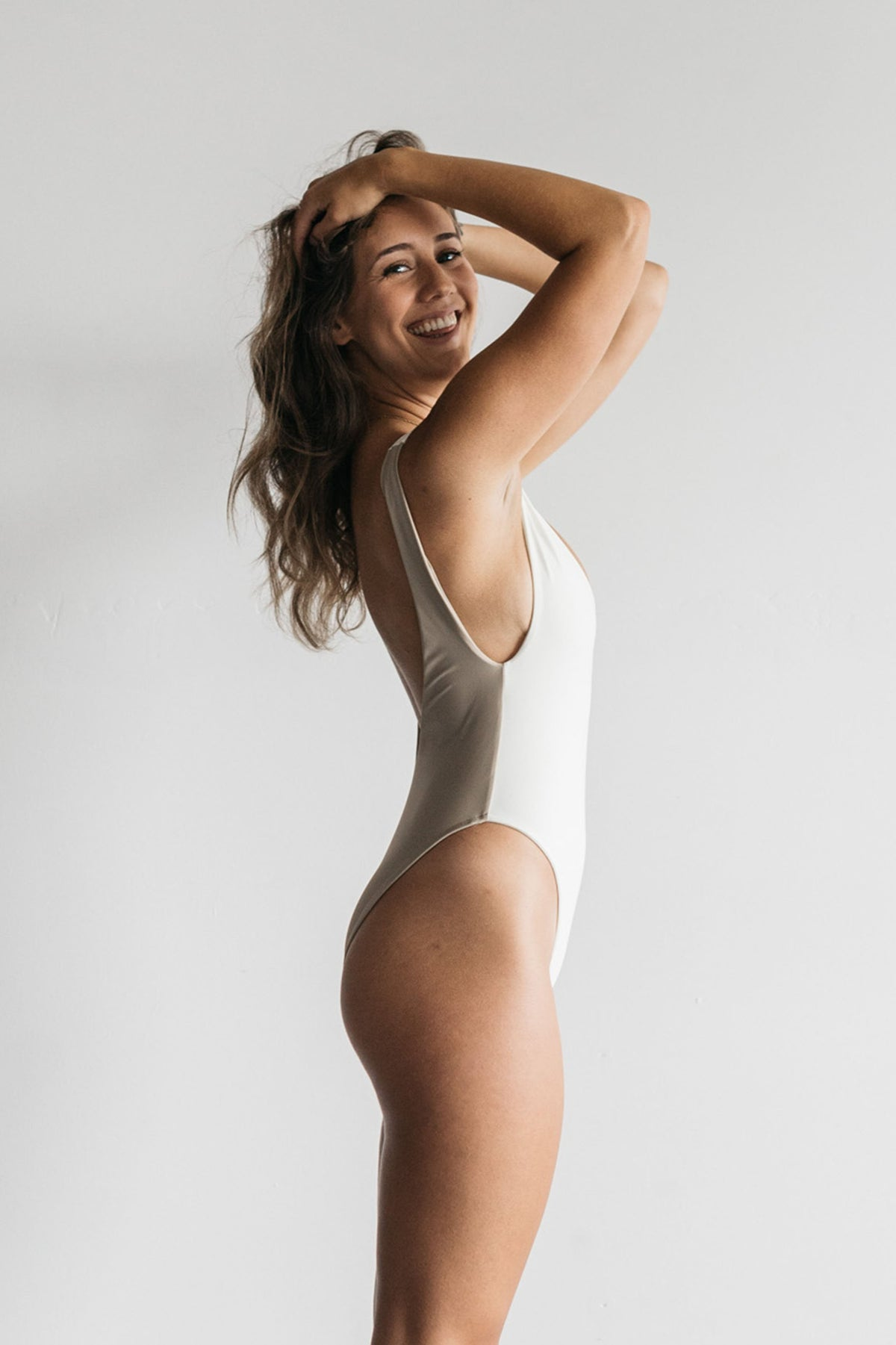 A woman standing to the side with her hands in her hair smiling wearing a white one piece swimsuit with a deep v neckline and minimal coverage.