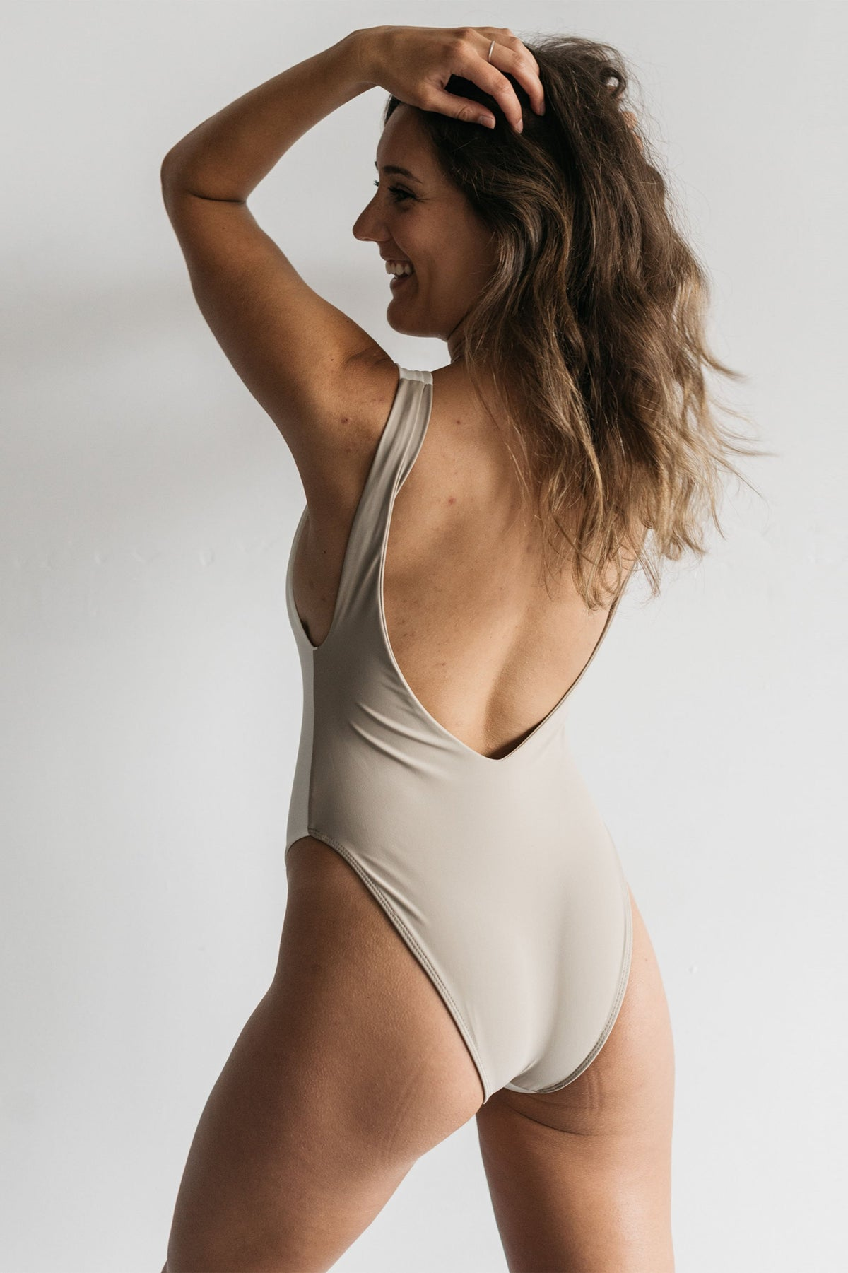 The back of a woman standing in front of a white wall with her hands in her hair looking to the side wearing a white and nude color blocked one piece swimsuit with a low back and minimal coverage.
