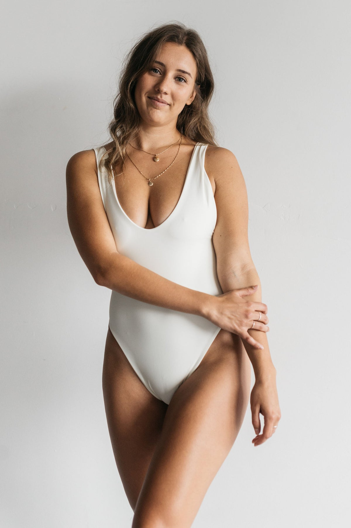 A woman standing with one arm crossed in front of her body wearing a white one piece swimsuit with a deep v neckline and minimal coverage.