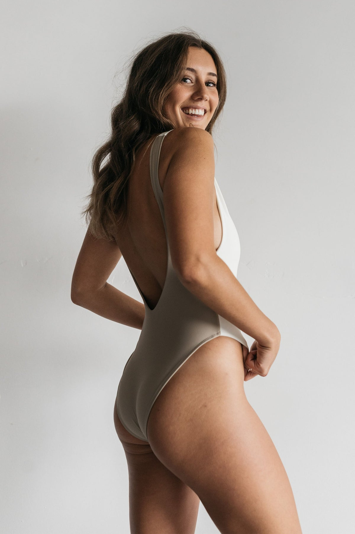 A woman smiling looking over her shoulder wearing a color blocked white and nude one piece swimsuit with a low back and minimal coverage.