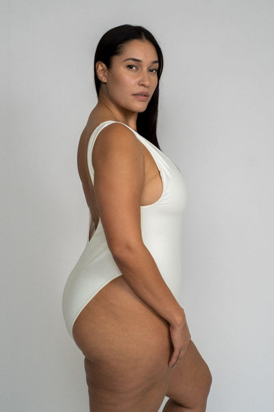 A woman standing to the side wearing a white one piece swimsuit with a v neckline and minimal coverage.