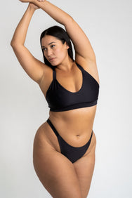 A woman leaning to the side with her arms stretched above her head wearing high cut cheeky black bikini bottoms and a matching black bikini top with a a scoop neckline.