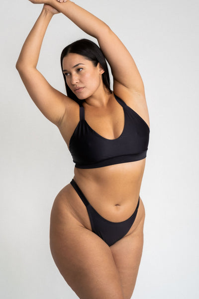 A woman standing with her arms above her head looking to the side wearing black high cut bikini bottoms and a matching black bikini top with a softly scooped neckline.