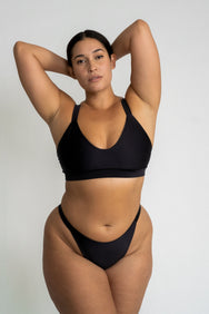 A woman standing with her arms folded above her head wearing high cut cheeky black bikini bottoms and a matching black bikini top with a a scoop neckline.