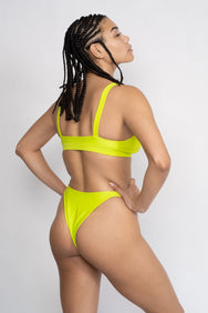 The back of a woman standing with her hands on her hips wearing neon green high cut minimal coverage bikini bottoms and a matching neon green bikini top.