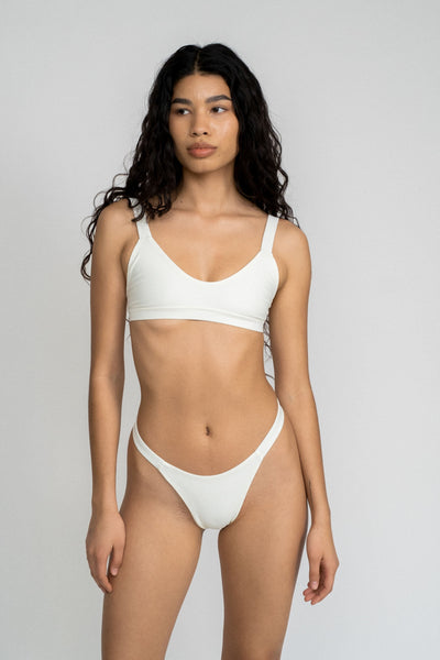A woman standing in front of a white wall wearing white high cut bikini bottoms and a matching white bikini top with a softly scooped neckline.