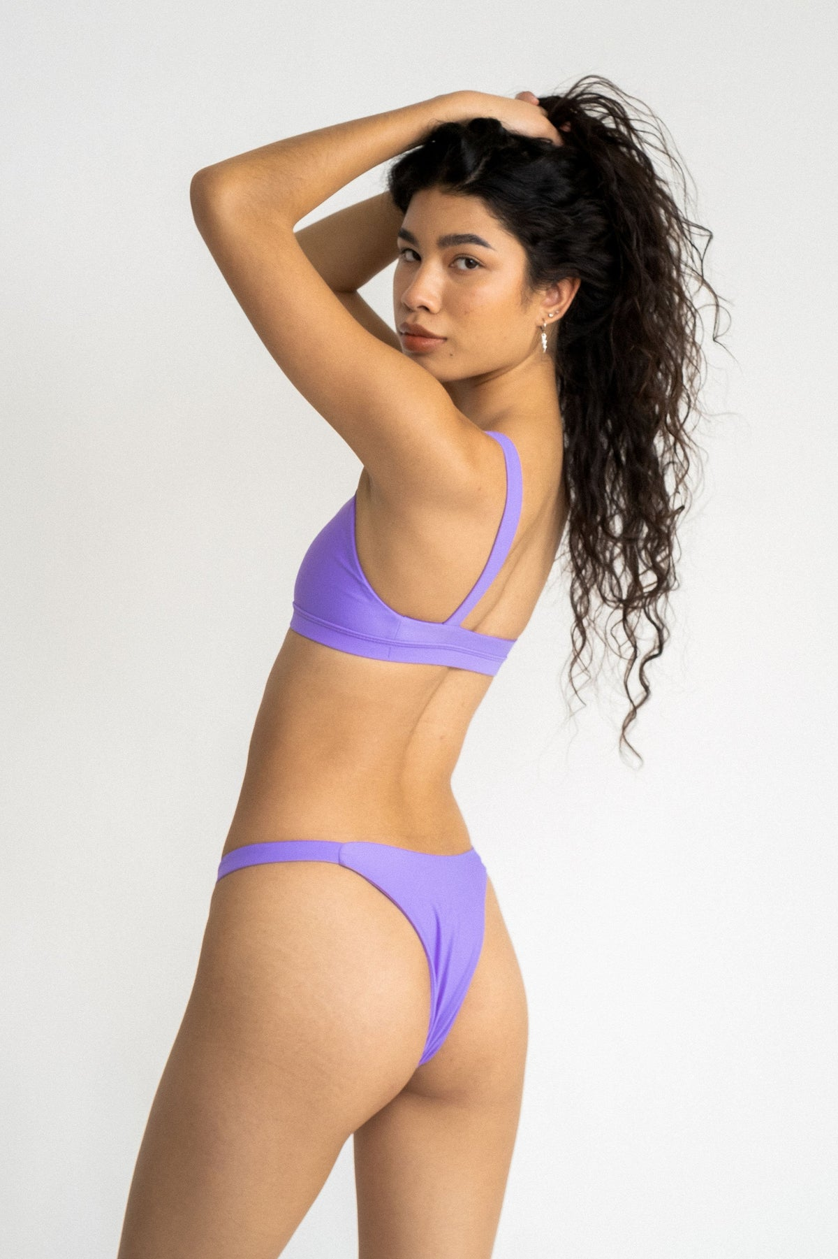 A woman turned to the side looking over her shoulder with her hands in her hair wearing bright purple high cut bikini bottoms and a matching bright purple bikini top.