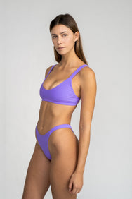 A woman standing to the side wearing high cut minimal coverage bright purple bikini bottoms and a matching bright purple bikini top with a scoop neckline.