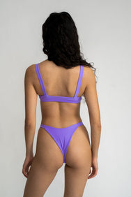 The back of a woman standing with bright purple cheeky minimal coverage bikini bottoms with a matching bright purple bikini top.