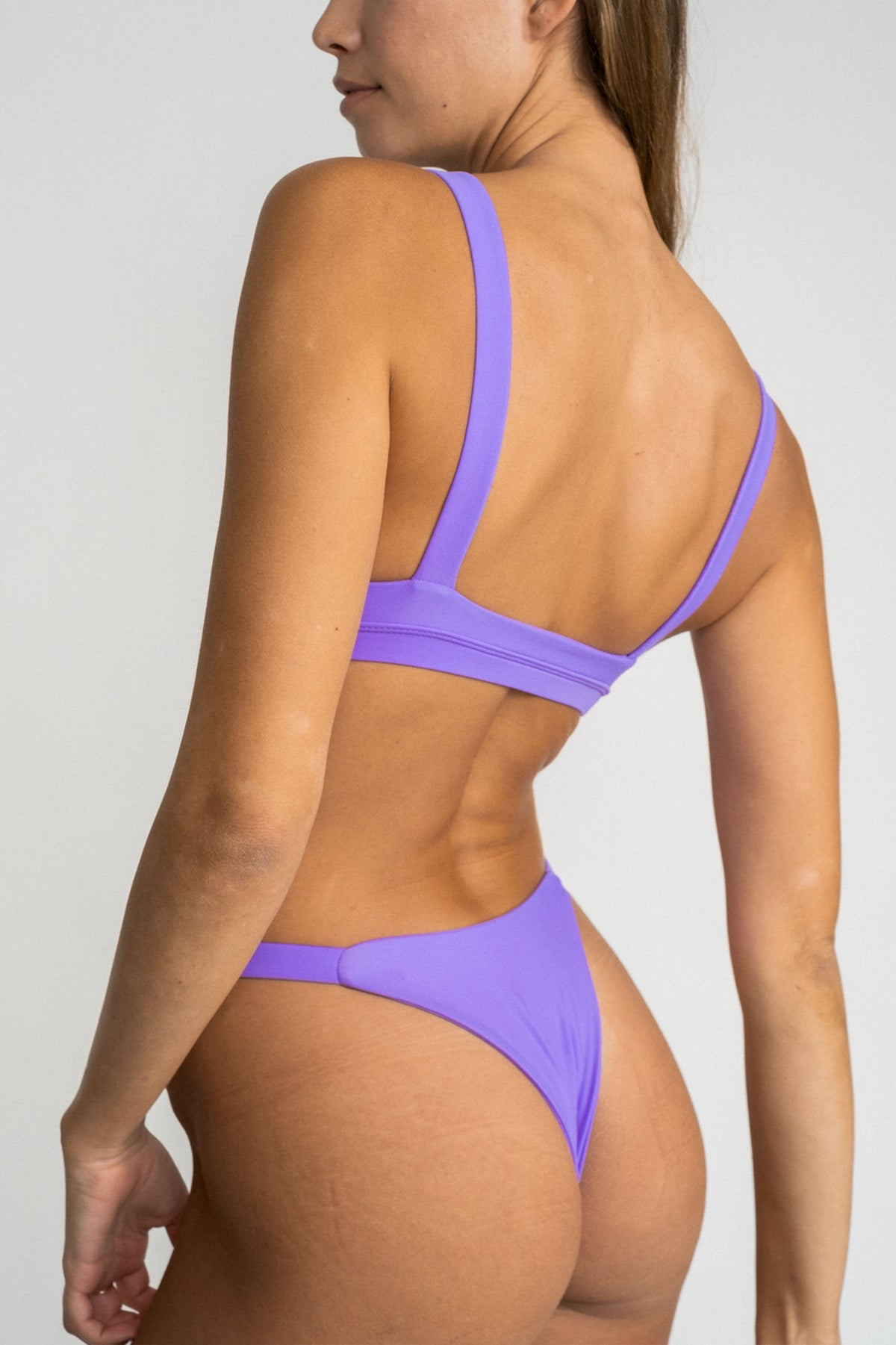 A close up of the back of a woman looking to the side wearing minimal coverage high cut bright purple bikini bottoms with a matching bright purple bikini top.