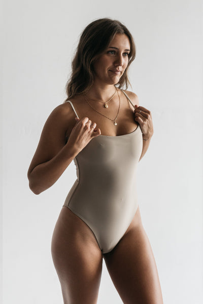 A woman standing with her hands on her shoulders wearing a nude one piece swimsuit with white spaghetti straps.