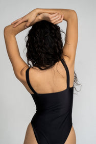 The back of a woman with her hands folded over her head wearing a black one piece swimsuit with minimal coverage.
