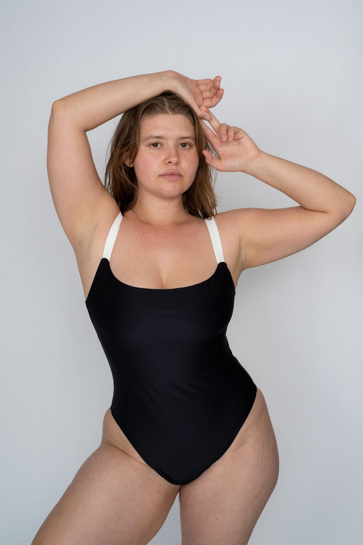 A woman standing with her hands above her head wearing a black one piece swimsuit with white thick spaghetti straps.
