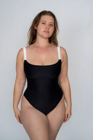 A woman standing wearing a black one piece swimsuit with white thick spaghetti straps.