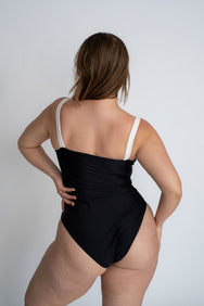 The back of a woman leaning to one side wearing a black one piece swimsuit with white thick spaghetti straps.