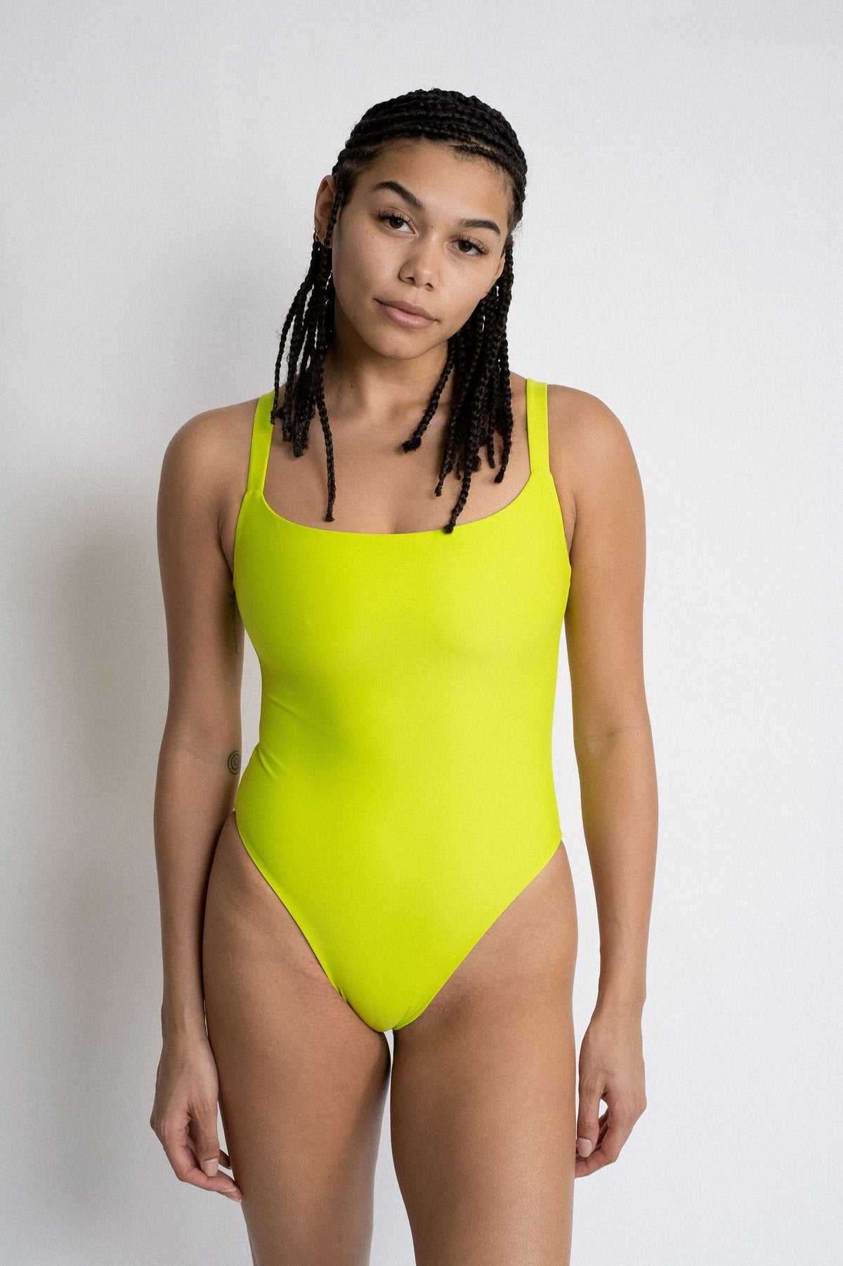 A woman standing in front of a white wall wearing a neon green one piece swimsuit with a straight neckline.