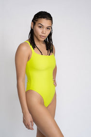 A woman standing with one hand on her hip wearing a neon green one piece swimsuit with a straight neckline.