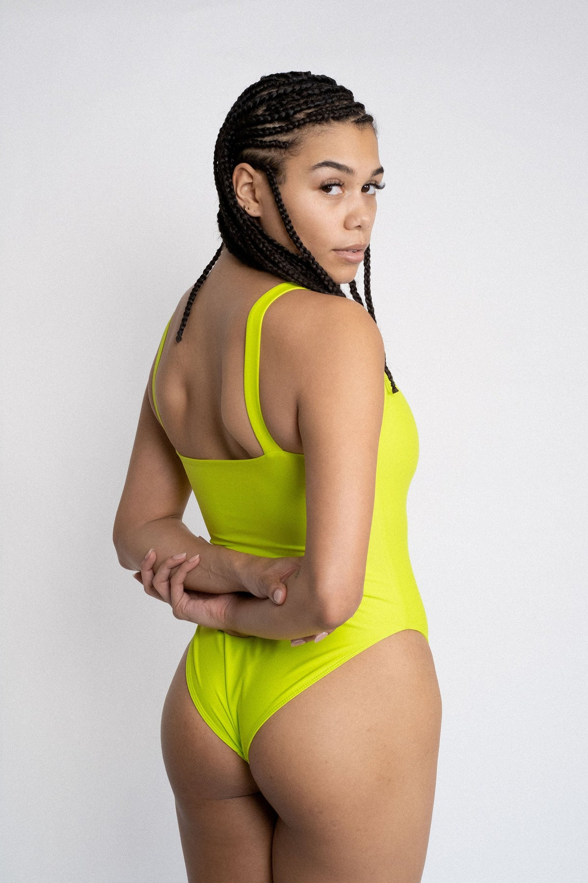The back of a woman looking over her shoulder with her hands crossed behind her wearing a neon green one piece swimsuit with minimal coverage.