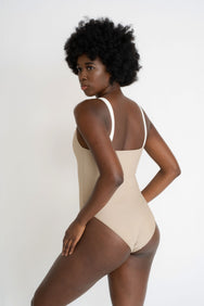 The back of a woman with her arms on her thighs looking over her shoulder wearing a nude one piece swimsuit with thick white spaghetti straps.