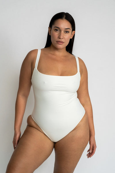 A woman standing with one leg pushed to the side wearing a white one piece swimsuit with a straight neckline.