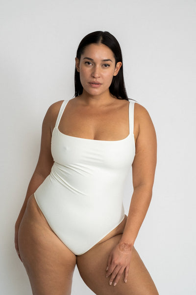 A woman standing leaning on one hip wearing a white one piece swimsuit with a straight neckline.