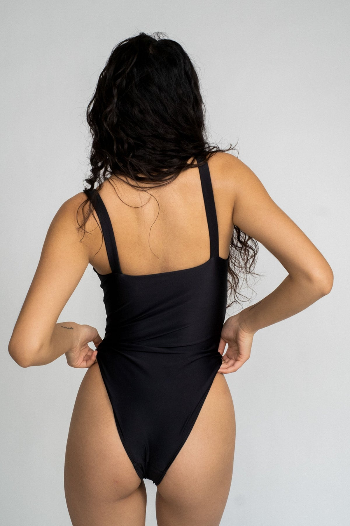 The back of a woman with her hands on her hips wearing a black one piece swimsuit with a straight neckline.